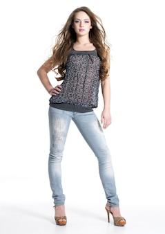 Volledige portret van mooi stijlvol meisje in mode stijlvolle jeans poseren geïsoleerd op wit. volledig lengteportret