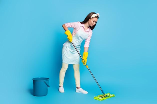 Volledige profielfoto aan de zijkant van een gefocuste professionele schoonmaakster, meisje, wasvloermop