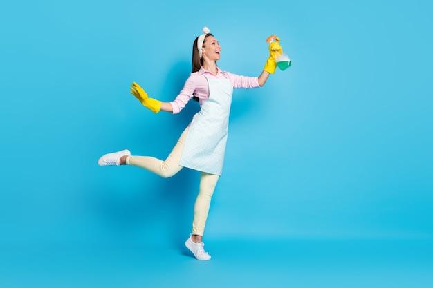 Volledige profielfoto aan de zijkant van een positieve, vrolijke meid houdt een spuitfles copyspace vast