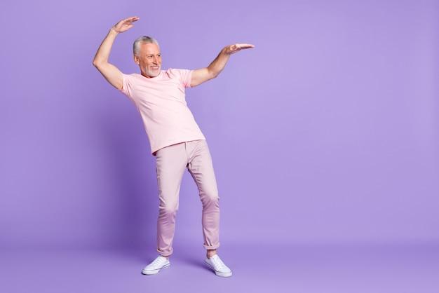 Volledige profielfoto van oude man dansende handpalmen kijken lege ruimte draag roze t-shirt broek sneakers geïsoleerde paarse kleur achtergrond