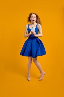 Volledige profielfoto van verraste roodharige dame die hoog springt en telefoon vasthoudt, lees schokb...