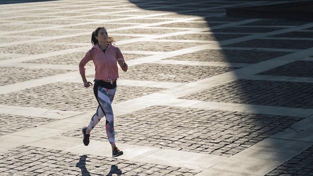 Volledige shot actieve vrouw joggen buiten