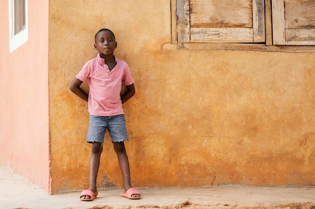 Volledige shot afrikaanse jongen buitenshuis