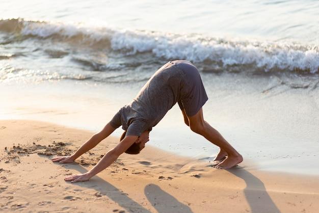 Volledige shot man beoefenen van yoga op het strand