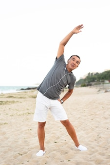 Volledige shot man die zich uitstrekt op het strand