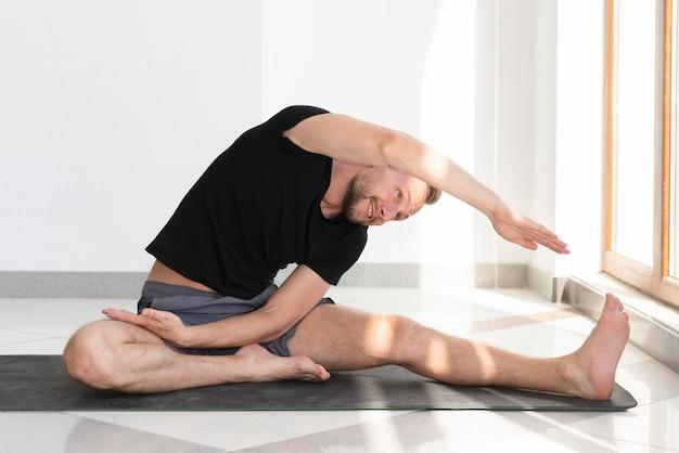 Volledige shot man die zich uitstrekt op yoga mat binnen