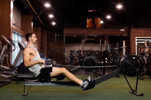 Volledige shot man training op sportschool zijaanzicht