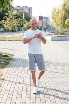 Volledige shot oudere man lopen kijken naar zijn telefoon