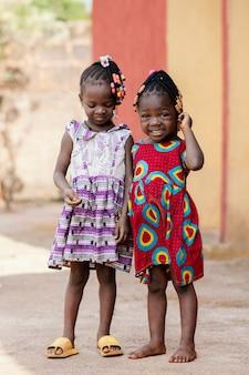 Volledige shot schattige afrikaanse meisjes buitenshuis