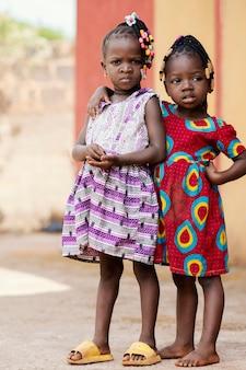 Volledige shot schattige afrikaanse meisjes poseren buitenshuis