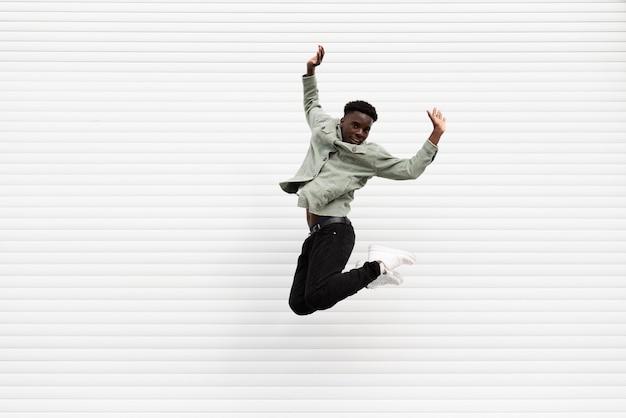 Volledige shot tiener springen voor foto