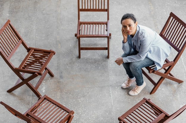 Volledige shot trieste vrouw zittend op een stoel