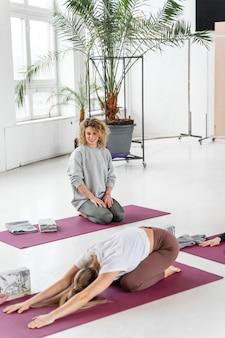 Volledige shot vrouw op yoga mat uitrekken