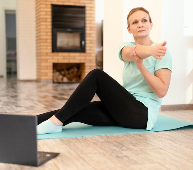 Volledige shot vrouw training met laptop binnenshuis