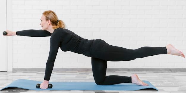 Volledige shot vrouw training op yogamat