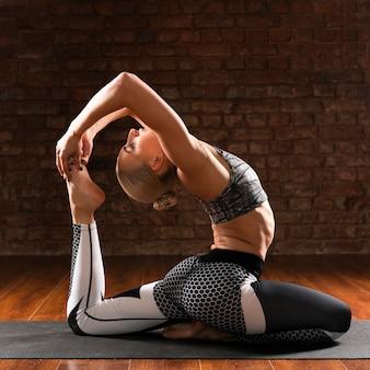 Volledige shot vrouw yoga specifieke houding