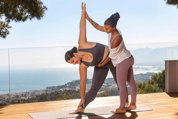 Volledige shot yogapraktijk met leraar