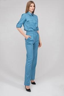 Volledige stockfoto van een prachtig slank en lang model met make-up en blond haar, gekleed in een elegant blauw shirt en broek met zwarte hakken. ze poseert op een witte achtergrond met de hand op de taille.