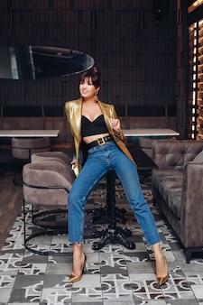 Volledige stockfoto van een prachtig slank model met donker haar in kapsel in crop top, gouden jas, jeans en stijlvolle gouden hakken poseren op tafel in modern interieur binnenshuis.