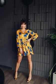Volledige stockfoto van een prachtige brunette met kapsel die een stijlvolle zijden jurk en hoge hakken draagt. poseren tegen donkergrijze muur binnenshuis.