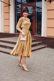 Volledige stockfoto van een prachtige elegante dame in gouden jurk, hoge hakken van gouden kleur en crossbag. ze loopt glimlachend op straat.