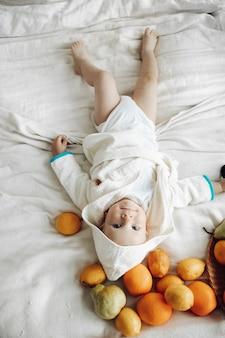 Volledige stockfoto van een schattige jonge jongen in een witte badjas die blootsvoets op wit bed ligt met verspreid fruit en glimlachend in de camera. citroenen, peren en sinaasappels verspreid over het bed in jongenshoofd.