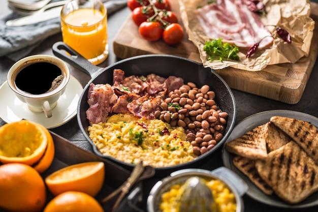 Volledige tafel met engels ontbijt. roerei gegrild spek bonen toast brood jus d'orange en koffie.