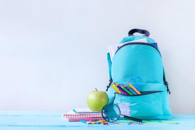 Volledige turquoise schoolrugzak met briefpapier op tafel.