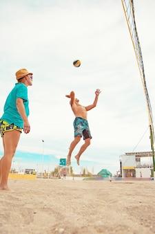 Volleybal strandspeler is een mannelijke atleet volleyballer die zich klaarmaakt om de bal op het strand te serveren.