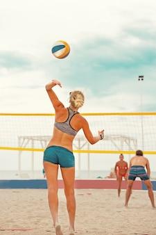 Volleybal strandspeler is een vrouwelijke atleet volleyballer die zich klaarmaakt om de bal op het strand te serveren.