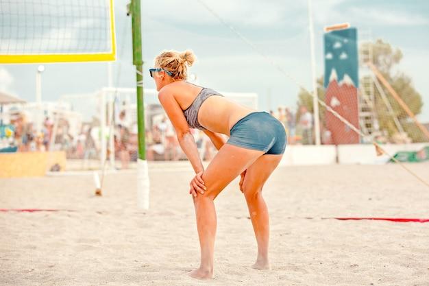 Volleybalstrandspeler is een vrouwelijke atleetvolleybalspeler die zich klaarmaakt om de bal op het strand te dienen