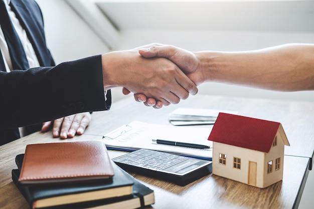 Voltooiing van succesvolle deal van onroerend goed, makelaar en cliënt handen schudden na ondertekening contract goedgekeurd aanvraagformulier, betreffende hypothecaire leningaanbieding en huisverzekering