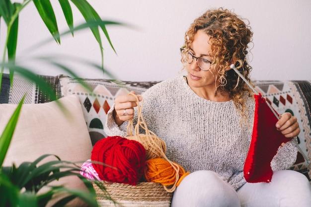 Volwassen aantrekkelijke vrouw thuis in het breien van werkactiviteit met behulp van kleurrijke wol. gelukkige en ontspannen vrouwelijke mensen genieten van tijd binnen op de bank. brei baan
