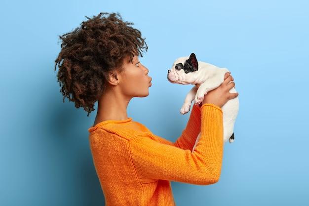 Volwassen afro-meisje staat in profiel, verhoogt kleine puppy in de lucht