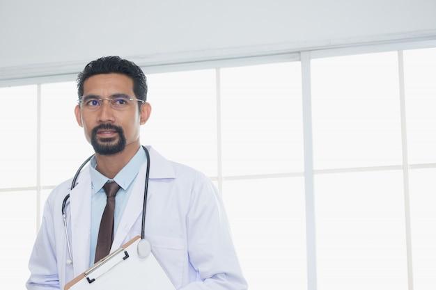 Volwassen arts die dokterstoga draagt met een stethoscoop die in de nek hangt met papierwerk dat staat en uitkijkt naar een betrouwbare manier