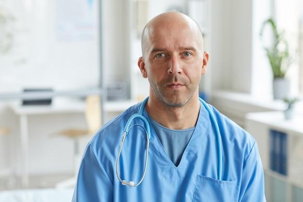 Volwassen arts draagt blauwe uniform met ernstige gezichtsuitdrukking