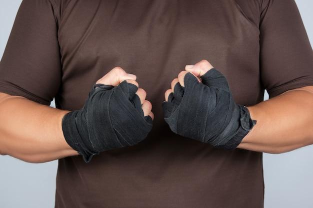 Volwassen atleet in bruin uniform staat in een rek met gespannen spieren