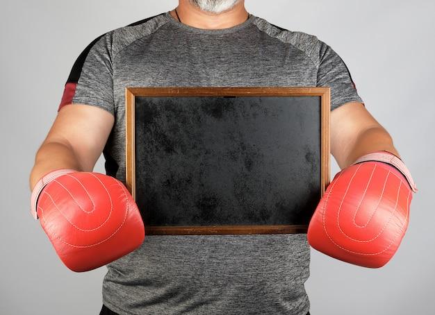 Volwassen atleet in grijze eenvormige en rode leer bokshandschoenen die een leeg zwart frame houden