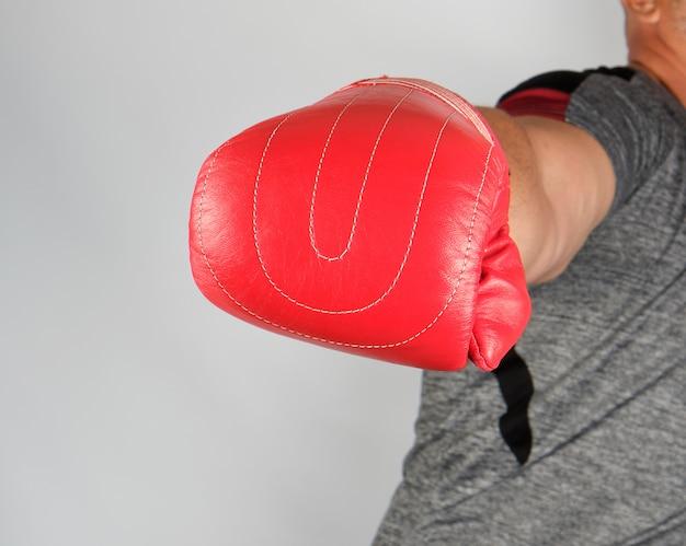 Volwassen atleet in grijze uniform en rode lederen handschoen valt naar voren