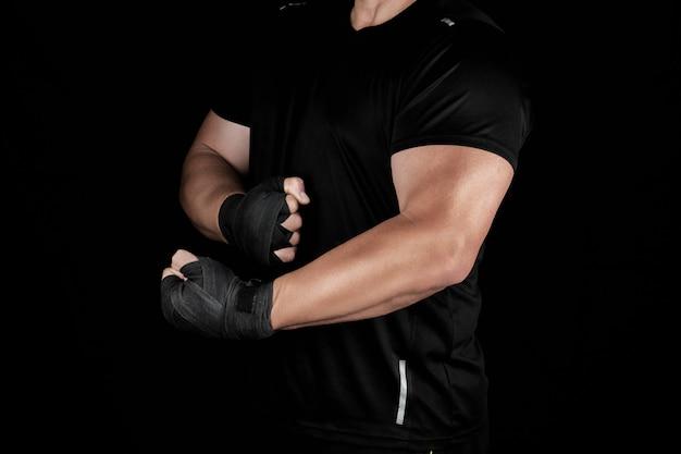 Volwassen atleet in zwart uniform staat in een rek met gespannen spieren