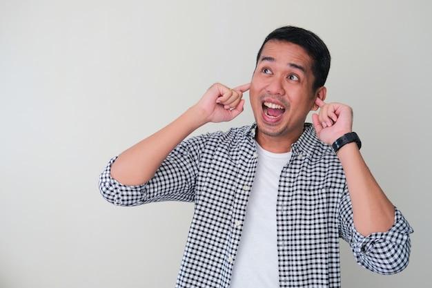 Volwassen aziatische man bedekt zijn oren met vinger en toont opgewonden gezichtsuitdrukking
