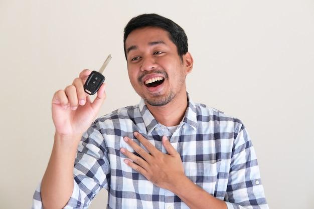 Volwassen aziatische man die blije uitdrukking toont terwijl hij naar zijn autosleutel kijkt