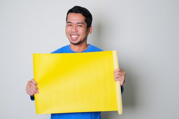 Volwassen aziatische man die gelukkig lacht terwijl hij blanco geel papier vasthoudt