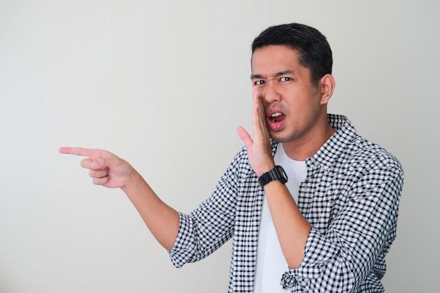 Volwassen aziatische man die roddels fluistert en met de vinger naar iemand wijst