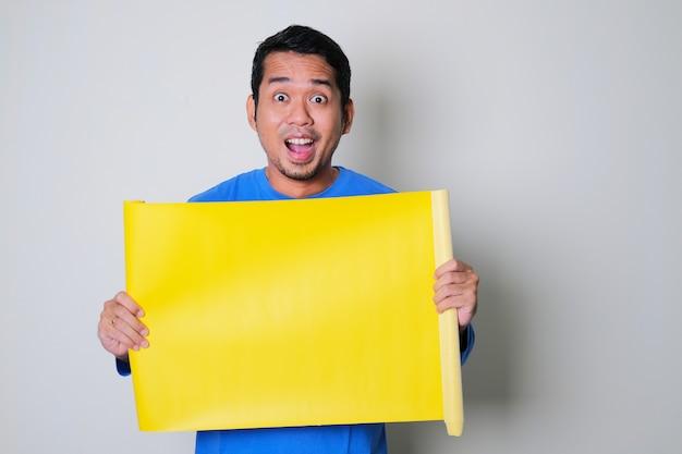 Volwassen aziatische man die verbaasde gezichtsuitdrukking toont terwijl hij leeg geel papier vasthoudt