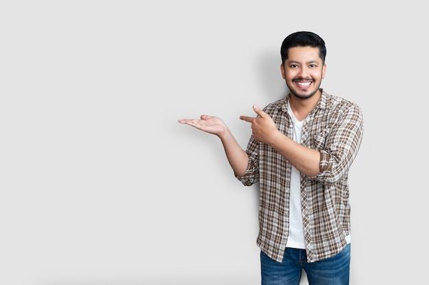 Volwassen aziatische man over geïsoleerde achtergrond glimlachend vrolijk presenteren en wijzen met palm van hand kijken naar de camera.