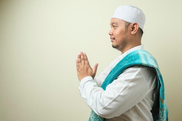 Volwassen aziatische moslimman gebaar ter begroeting en gastvrije gast voor eid mubarak