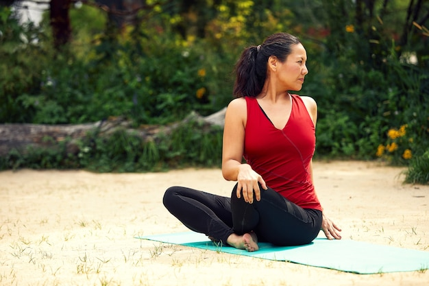 Volwassen aziatische vrouw die yoga in de natuur doet, rek- en flexibiliteitsoefeningen doet, yogales voor volwassen vrouwen