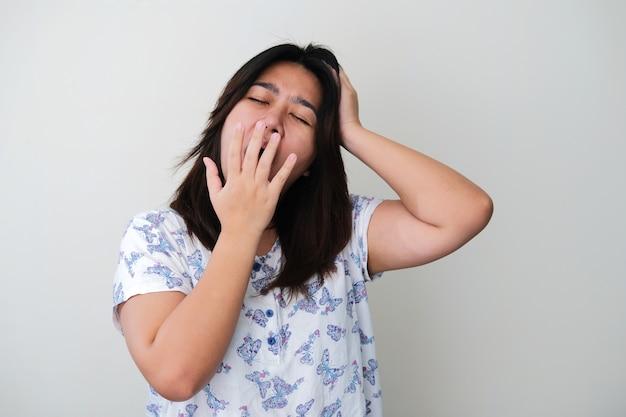 Volwassen aziatische vrouw geeuwen met gesloten ogen
