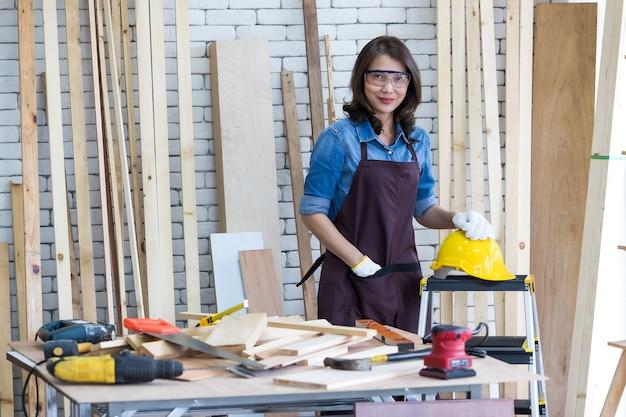 Volwassen aziatische vrouw met helm en bril die naar de camera kijkt terwijl ze in de buurt van houten planken in schrijnwerk zit